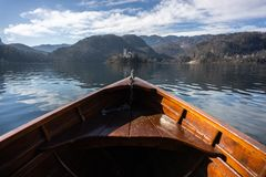 Wooden rent boat, end of the boat facing towards Lake Bled island - copy space and focus on Bled island, tourist stock photo