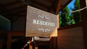 Wooden reserved table on steel chains, white printed letters on timber board, table reserved. Wooden reserved table on steel chains, white printed letters on stock video footage