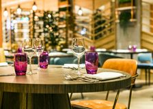Restaurant table set up for casual dining meal. Wooden restaurant table and leather chairs set up for casual dining meal with natural light flower wall and stock image