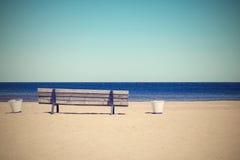 Wooden retro bench on the sandy beach seashore Stock Images