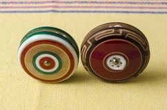 Wooden retro yoyos on yellow tablecloth. Traditional mexican toys