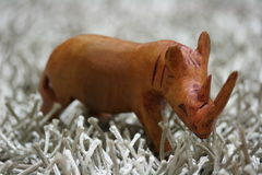Wooden hand carved rhinoceros toy. Closeup of wooden hand carved rhinoceros toy on silver field Stock Photography