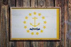 Wooden Rhode Island flag. 3d rendering of a Rhode Island State USA flag on a wooden frame and a wood wall Royalty Free Stock Photo