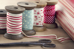Wooden ribbon spools, paper rolls and old scissors Royalty Free Stock Photo