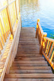 Wooden river dock. Descent to the water in the rays of the setting sun. Wooden river dock. Descent to the water in the rays of the sunset Royalty Free Stock Photography