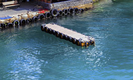 Wooden river pier for small boats with used tires as bumpers Stock Image