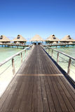 The wooden road over the sea to traditional lodges on piles Royalty Free Stock Images
