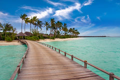 Wooden road over the sea to the tropical island. Stock Photography
