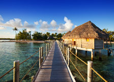 The wooden road over the sea to the tropical island. Royalty Free Stock Photo