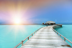 The wooden road over the sea to the tropical island Stock Photo