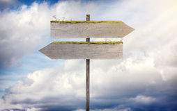 Wooden road sign with left and right arrows. And wonderful sky Stock Photos