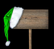 Wooden road sign with Santa hat. Isolated on a black background Royalty Free Stock Photography