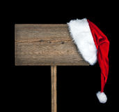Wooden road sign with Santa  hat. On black background Stock Photos