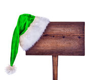 Wooden road sign with Santa  hat. Isolated on a white background Royalty Free Stock Photos