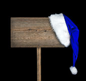 Wooden road sign with Santa  hat. Isolated on a black background Royalty Free Stock Images