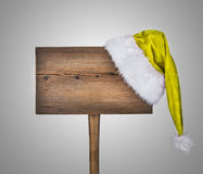 Wooden road sign with Santa  hat. On grey background Stock Photos