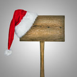 Wooden road sign with Santa  hat. Isolated on a gray background Stock Photos