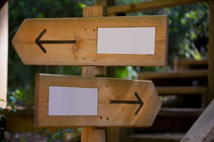 Wooden road sign with two opposite arrow directions Royalty Free Stock Image