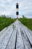 Lighthouse on the shore. Wooden road, to the lighthouse on the island Stock Photos