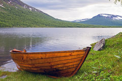 Wooden rowboat at Lapland lake. Royalty Free Stock Photo