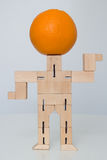 Wooden Robot Toy. With orange on head at white Royalty Free Stock Image