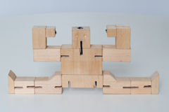 Wooden Robot Toy. Robot sitting on the splits on white Royalty Free Stock Photo