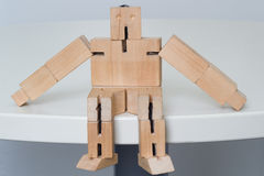 Wooden Robot Toy. Sitting at white table Stock Image