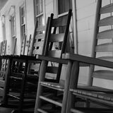 Wooden rocking chairs lined up on a porch. An up close photo of wooden rocking chairs lining an old country porch royalty free stock photos