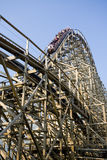 Wooden rollercoaster. With a cart coming down the steep part. The cart is in motion/blurry so you cannot see who is on it Royalty Free Stock Photography