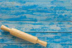 Wooden rolling pin on blue wooden table. Top view Stock Photos
