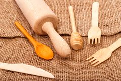 Wooden rolling-pin, fork, knife and spoon Stock Image