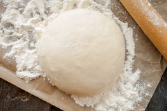 Wooden rolling pin with freshly prepared dough for pizza Royalty Free Stock Photo