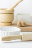 Wooden rolling pin, mortar and pestle, honey dipper, baking form and cutting board on white tabletop. Minimalist styled image. Stock Photo