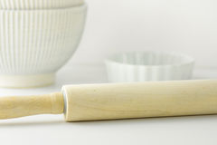 Wooden rolling pin, white bowl and baking form on table top. Pastry, cooking, bakery concept. Clean minimalist style. Template for Royalty Free Stock Images