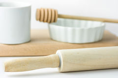Wooden rolling pin, white measuring cup, baking form and honey dipper on cutting board. White tabletop background. Royalty Free Stock Photos
