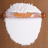 Wooden rolling pin with white wheat flour on the table Royalty Free Stock Photography