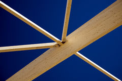 Wooden roof beams. A view looking up at wooden roof beams or rafters and blue sky on a new building construction site Stock Photos