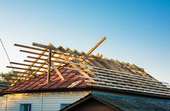 Construction of a wooden roof. External work on the building envelope. Remodeling of old roof. Wooden Roof Frame House Construction. Wooden rafters of new roof stock photography