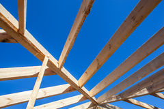Wooden roof rafters over bright sky. Rafters over blue bright sky background royalty free stock image