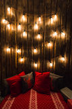 Wooden room in rustic house with wall and designer light bulbs, decorated place for seat. Red gray pillows. Royalty Free Stock Photography