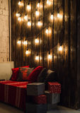 Wooden room in rustic house with wall and designer light bulbs, decorated place for seat. Red gray pillows. Royalty Free Stock Images