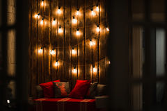 Wooden room in rustic house with wall and designer light bulbs, decorated place for seat. Red gray pillows. Royalty Free Stock Photo