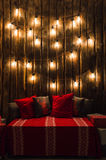 Wooden room in rustic house with wooden wall and designer light bulbs, decorated place for seat. Red gray pillows. Stock Images