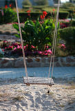 Wooden rope swing above the sand against the flowerbed Stock Photo