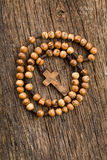 Wooden rosary beads. On old wooden background royalty free stock photography
