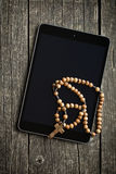 Wooden rosary beads with computer tablet Stock Photos