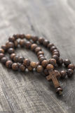 Wooden rosary beads on old wooden background Stock Image