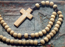 Wooden rosary on the book. Wooden beads with a cross lying on an old Bible Stock Photography