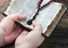 Wooden rosary and a Christian cross in his hand Royalty Free Stock Image