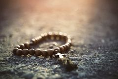 Wooden rosary with a cross lying on the pavement, illuminated by sunlight. Forgotten lost wooden rosary with a cross lying on the pavement, illuminated by royalty free stock image